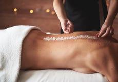 Female therapist make salt massage to young lady stock photo