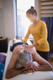 Female therapist massaging back of senior male patient against window Royalty Free Stock Photography