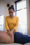 Female therapist massaging back of senior male patient lying on bed Stock Photo