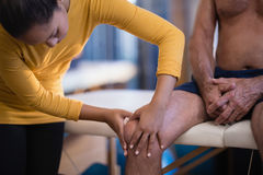 Female therapist massaging knee of senior male patient sitting on bed Royalty Free Stock Photo