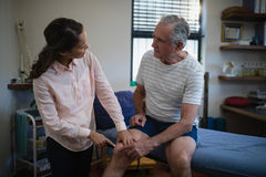 Female therapist pointing at knee while talking with senior male patient. In hospital ward Stock Images