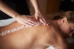 Female therapist put mineral salt on lady back royalty free stock photo