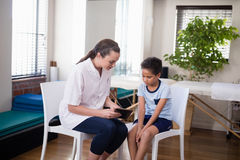 Female therapist showing digital tablet to boy sitting on chairs. At hospital ward Royalty Free Stock Photos
