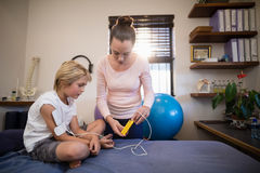 Female therapist showing electrical muscle stimulation machine to boy sitting on bed. At hospital ward royalty free stock photos