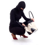 Female thief in black balaclava with bag Stock Photo