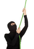 Female thief climbing on green rope Stock Image