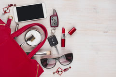 Female things and red handbag on wooden background with copyspace Royalty Free Stock Photos