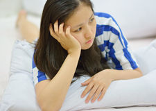 Female thinking  while lying on the bed  Royalty Free Stock Photography