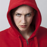Female threat concept for angry 20s streetwear girl. Female threat concept - angry 20s girl wearing streetwear with hooded sweatshirt expressing teen arrogance royalty free stock images