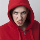 Female threat concept for rebellious girl wearing streetwear. Female threat concept - rebellious 20s girl wearing streetwear with hooded sweater expressing stock photo