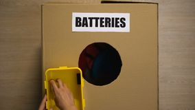 Female throwing used batteries in box for recycling, heavy metals disposing. Stock footage stock video footage