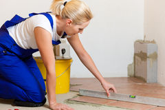Female tiler tiling tiles on the floor Stock Photography