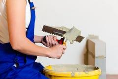 Female tiler tiling tiles on the floor Stock Image