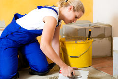 Female tiler tiling tiles on the floor Royalty Free Stock Photos