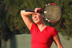 Female tired woman tennis player, racket. Wipes sweat. Female tennis player with tennis racket that wipes the sweat from his forehead. A woman tennis player. She Royalty Free Stock Photos
