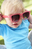 Female Toddler Trying To Put On Sunglasses Royalty Free Stock Images