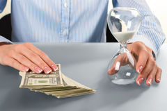 Female touches cash and hourglass. Stock Image