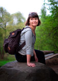 Female tourist. Sitting on a stone in the forest Stock Photography