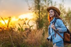 Female tourist with backpack and camera in countryside with sunset stock photo