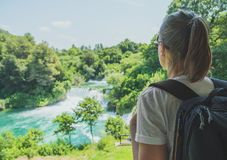 Female tourist. Female tourist with backpack looking at waterfalls royalty free stock photo