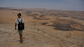 Female tourist with backpack walking along mountain rock cliff edge stock footage