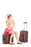 Female tourist in bikini sitting on her luggage Stock Image