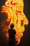 Female tourist in black clothing standing and looking at contemporary art of human face. Fantastic color lighting on human face. stock photos