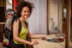 Female tourist buys a ticket at terminal station ticket counter. Beautiful female backpacker tourist buys a ticket for her journey at terminal station ticket royalty free stock image
