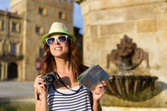 Female tourist with camera and guide map sightseeing. Funky woman on summer vacation travel visiting typical spanish landmark in Asturias. Female tourist taking royalty free stock photography