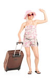 Female tourist carrying her luggage Stock Photo