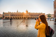 Female tourist in the center of Krakow. Young female tourist with camera and backpack photographing Cloth Hall in the old city center of Krakow royalty free stock image