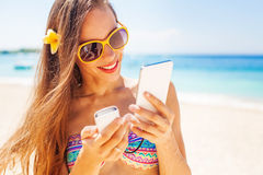 Female tourist charging her phone on a beach Stock Photos