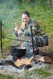 Female tourist cooking food in cauldron. Female tourist cooking fresh food in cauldron at camp on open fire royalty free stock photos