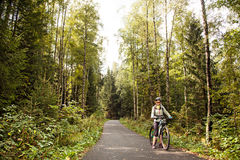 Female tourist cyclist  standing on road in forest, looking to c Royalty Free Stock Photography