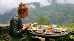 Female tourist eating breakfast Royalty Free Stock Image