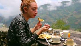 Female tourist eating breakfast stock footage