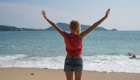 Female tourist enjoying summertime on beautiful tropical island. Back view of female tourist in red shirt and blue shorts standing on the beach with raised hands stock photo