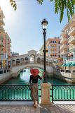 Female tourist enjoys the view to the Qanat Quartier on the Pearl in Doha Stock Photo