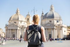 Female tourist with a fashinable vintage hipster backpack on Piazza del Popolo in Rome, Italy. Stock Photography