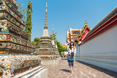 Female tourist girl visiting famous wat pho temple. Happy elegant female tourist girl visiting famous wat pho temple and walking on walkway viewing macro royalty free stock photography