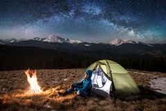 Female tourist have a rest in her camp at night under beautiful sky full of stars and milky way Stock Images