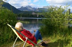 A 60+ female tourist and hiker enjoying a view of the lake and mountains from her deck chair Stock Photography