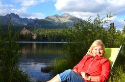A 60+ female tourist and hiker enjoying a view of the lake and mountains from her deck chair Stock Image