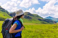 Female tourist hiking in mountains. Young female tourist with backpack walking mountain trail stock images