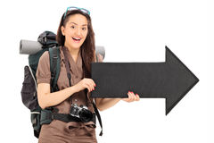 Female tourist holding an arrow pointing right Stock Image