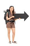 Female tourist holding a black arrow pointing right Royalty Free Stock Images