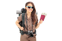 Female tourist holding a passport full of money Royalty Free Stock Images