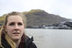 Female tourist in Iceland posing with Mountains in the background. aged 20-25, blonde hair. Copy space on right side. Good photo for travel websites featuring royalty free stock photography