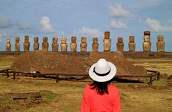 Female tourist impressed by the ruins of Moai statues at Ahu Tongariki on Easter Island archaeological site, Chile. South America royalty free stock images