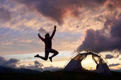 Female tourist jumping high adoring beautiful scenery around on moutain hill in Romania. Girl woman climber tent night clouds magnificent breathtaking Royalty Free Stock Photography